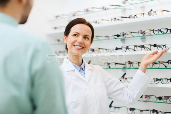 optician showing glasses to man at optics store Stock photo © dolgachov