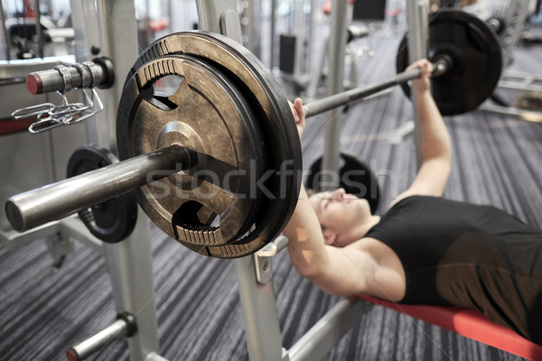 close up of man flexing biceps with barbell in gym Stock photo © dolgachov