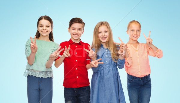 happy boy and girls showing peace hand sign Stock photo © dolgachov