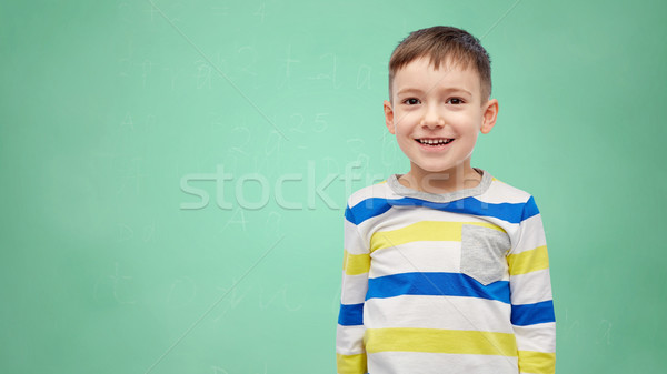 happy smiling little boy over green school board Stock photo © dolgachov