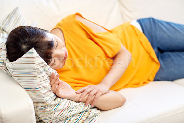 happy asian teenage girl sleeping on sofa at home Stock photo © dolgachov