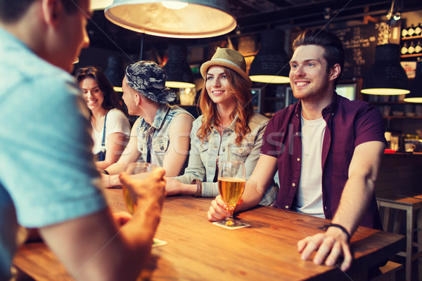 happy friends drinking beer and talking at bar Stock photo © dolgachov