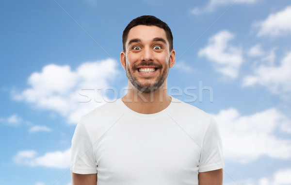 man with funny face over blue sky background Stock photo © dolgachov