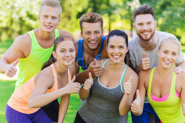 group of happy sporty friends showing thumbs up Stock photo © dolgachov