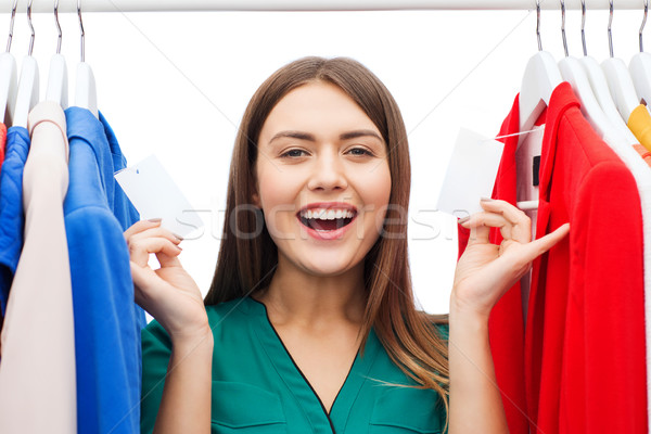 happy woman with sale tags on clothes at wardrobe Stock photo © dolgachov