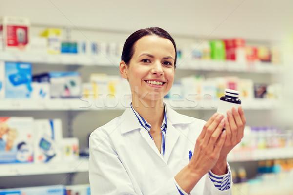 happy female pharmacist with drug jar at pharmacy Stock photo © dolgachov