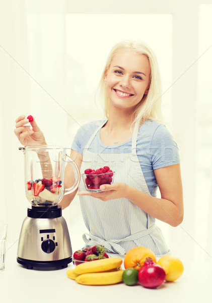 smiling woman with blender preparing shake at home Stock photo © dolgachov