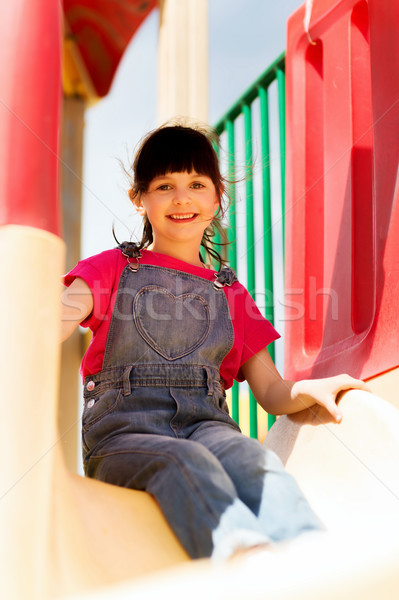 happy little girl on slide at children playground Stock photo © dolgachov