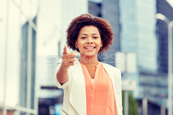 happy african businesswoman pointing finger on you Stock photo © dolgachov