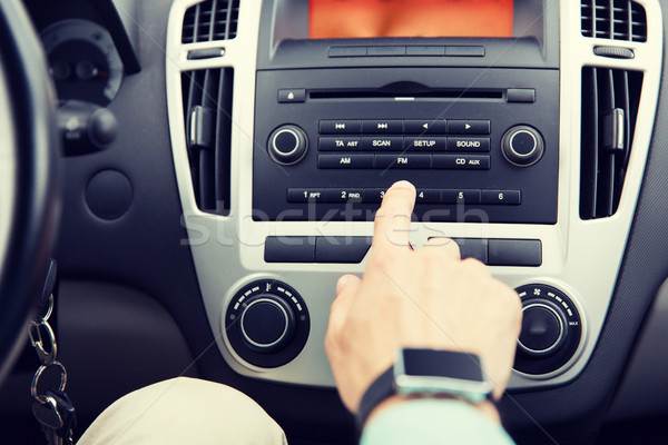close up of male hand turning on radio in car Stock photo © dolgachov