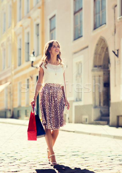 happy woman with shopping bags walking in city Stock photo © dolgachov