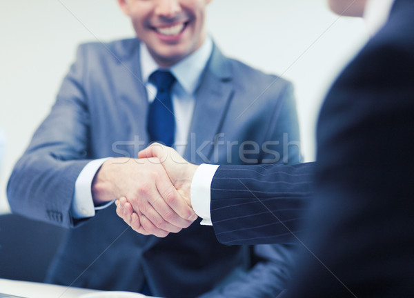 Stock photo: two businessmen shaking hands in office