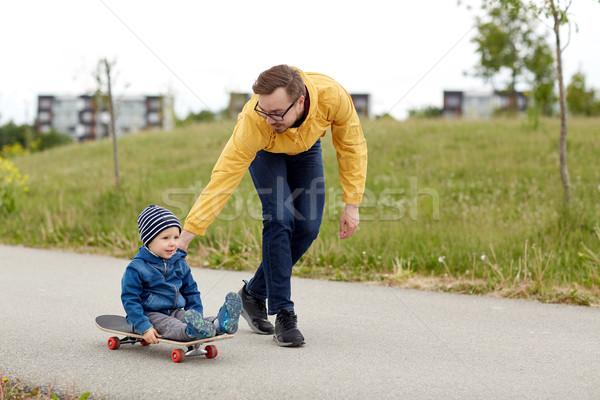 Heureux père peu fils équitation skateboard Photo stock © dolgachov