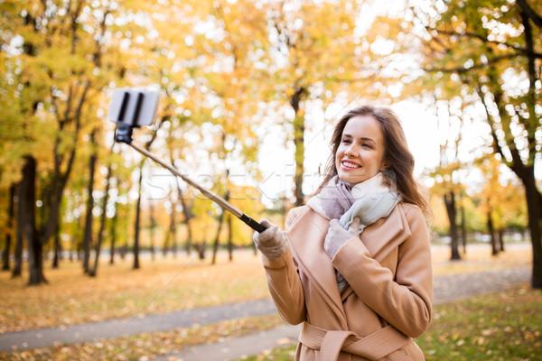 woman taking selfie by smartphone in autumn park Stock photo © dolgachov