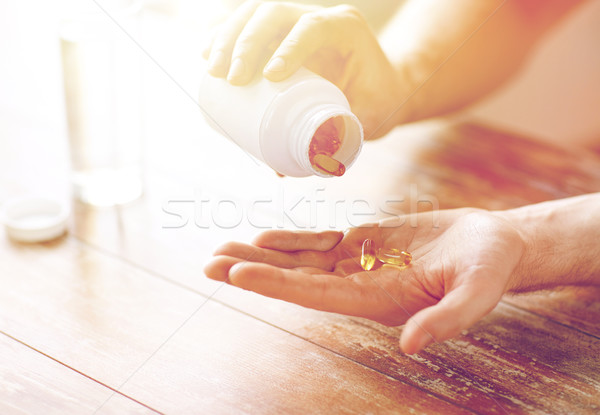 close up of man pouring fish oil capsules to hand Stock photo © dolgachov