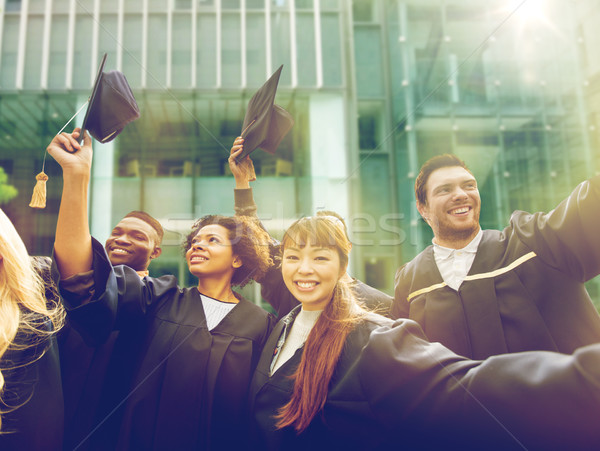 happy students or bachelors waving mortar boards Stock photo © dolgachov