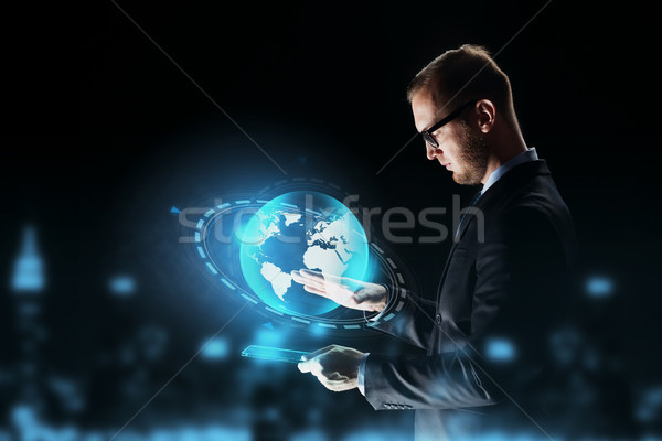 businessman with tablet pc and earth hologram Stock photo © dolgachov
