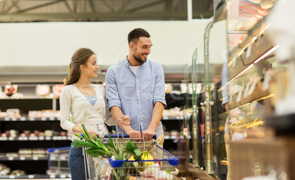 couple with food in shopping cart at grocery store Stock photo © dolgachov