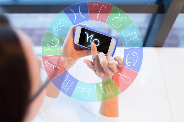 woman with smartphone and zodiac signs at office Stock photo © dolgachov