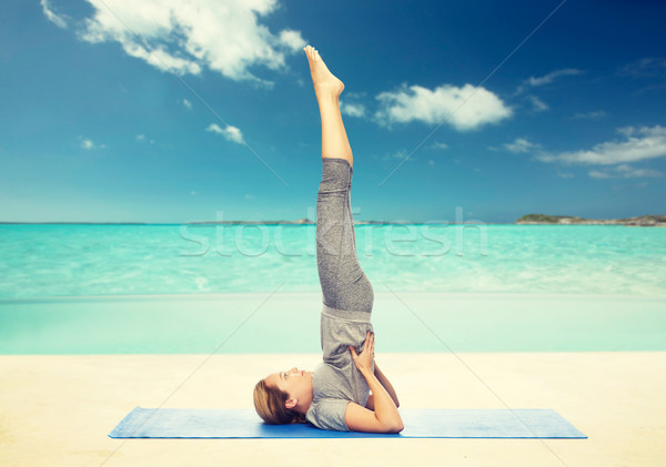 woman making yoga in shoulderstand pose on mat Stock photo © dolgachov