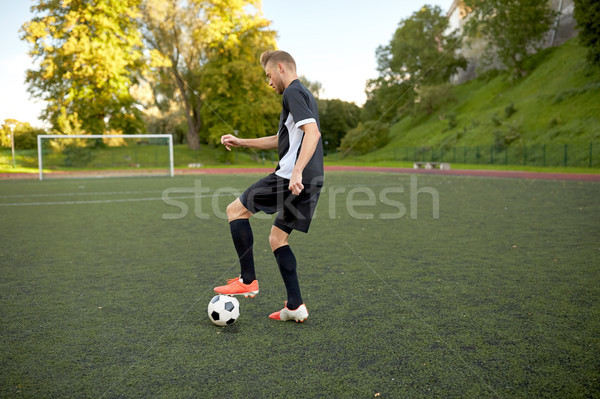 soccer player playing with ball on football field Stock photo © dolgachov