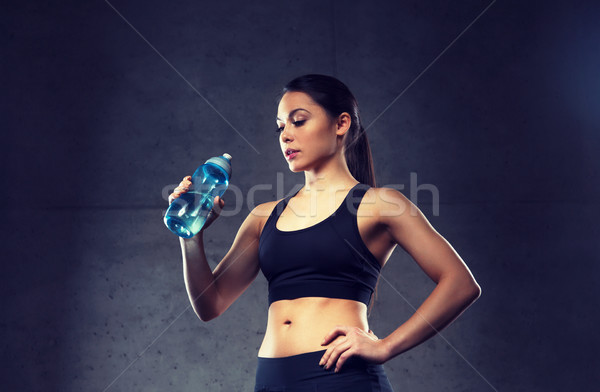woman drinking water from bottle in gym Stock photo © dolgachov