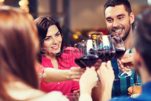 friends clinking glasses of wine at restaurant Stock photo © dolgachov