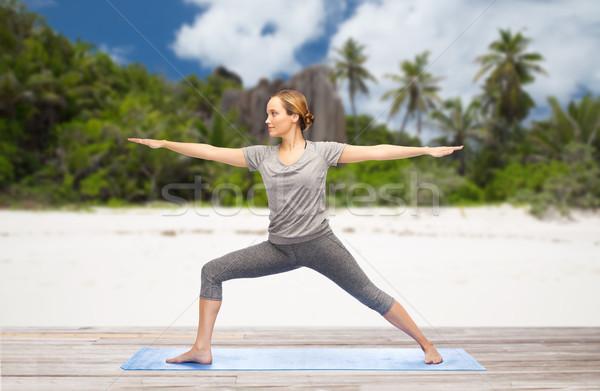 Vrouw yoga krijger pose strand fitness Stockfoto © dolgachov