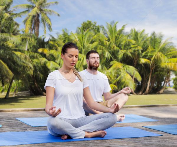 people meditating in yoga lotus pose outdoors Stock photo © dolgachov