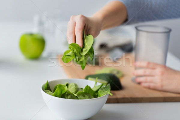 close up of woman hand adding spinach to bowl Stock photo © dolgachov