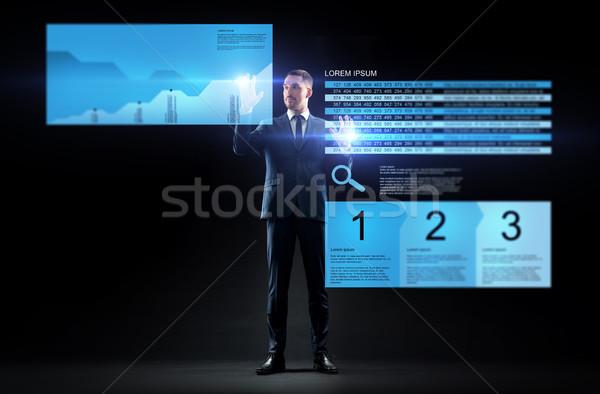 businessman with stock charts on virtual screens Stock photo © dolgachov