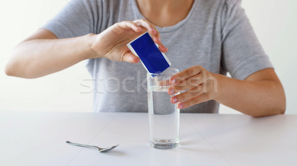 woman pouring medication into glass of water Stock photo © dolgachov