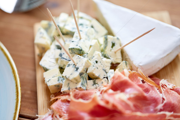blue cheese and jamon or parma ham on wooden board Stock photo © dolgachov