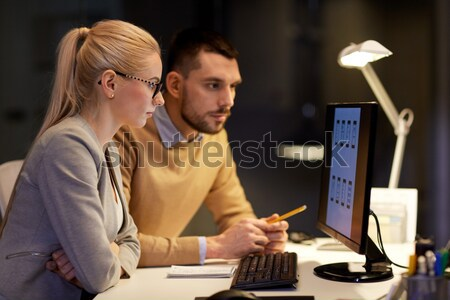 man with papers and computer works at night office Stock photo © dolgachov
