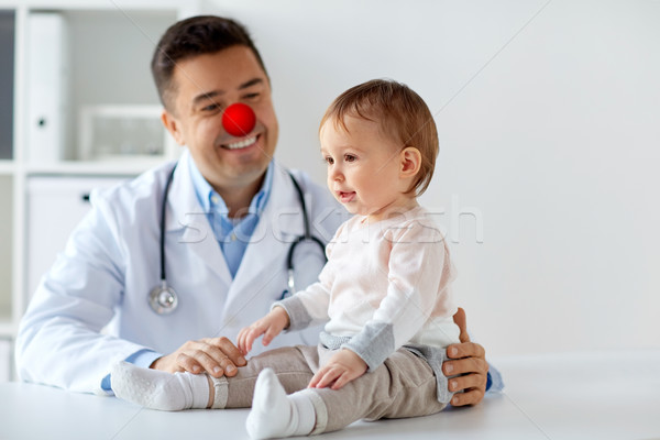 happy baby girl at doctor on red nose day Stock photo © dolgachov