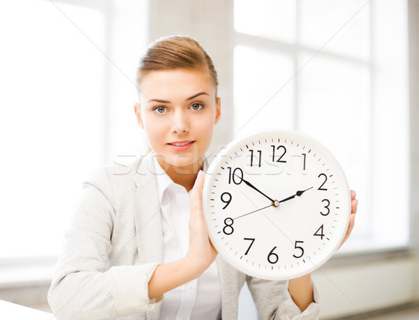 attractive businesswoman showing white clock Stock photo © dolgachov