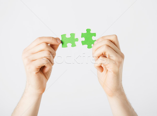 two hands trying to connect puzzle pieces Stock photo © dolgachov