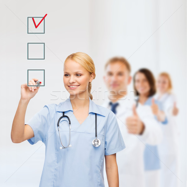 doctor or nurse drawing checkmark into checkbox Stock photo © dolgachov