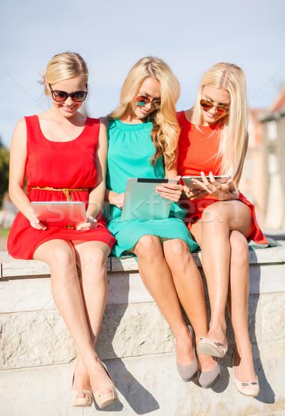 beautiful girls toursits looking into tablet pcs Stock photo © dolgachov