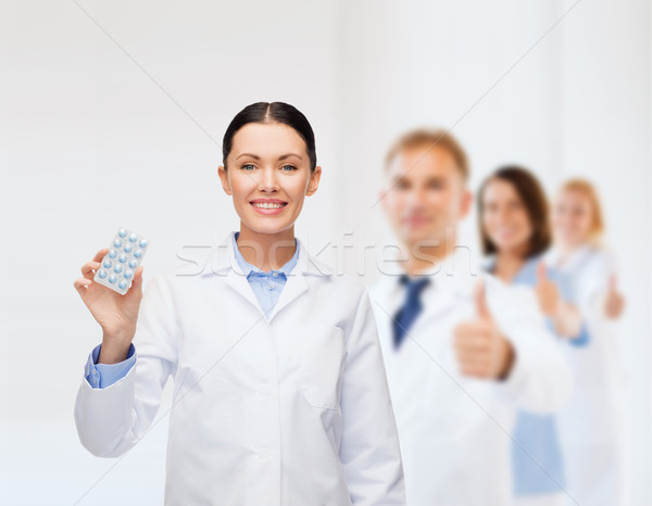 smiling female doctor with pills Stock photo © dolgachov