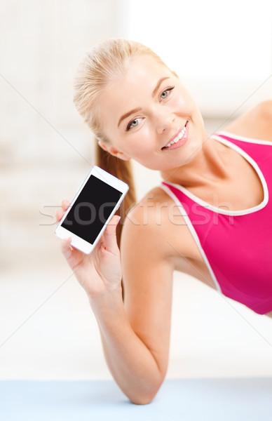 Glimlachende vrouw vloer smartphone fitness technologie oefening Stockfoto © dolgachov