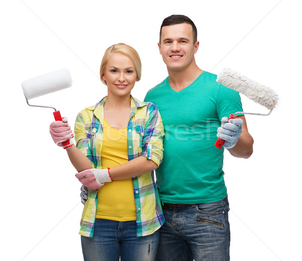 smiling couple in gloves with paint rollers Stock photo © dolgachov