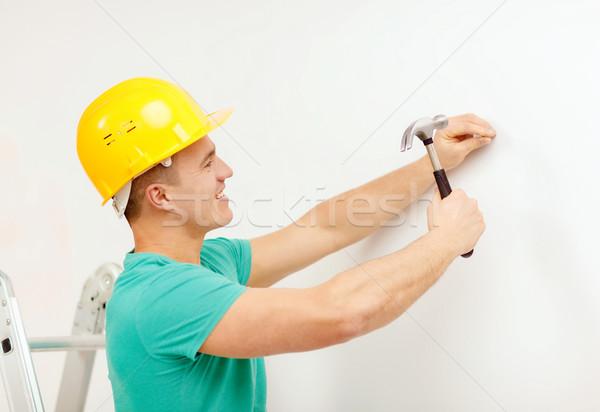 smiling man in helmet hammering nail in wall Stock photo © dolgachov