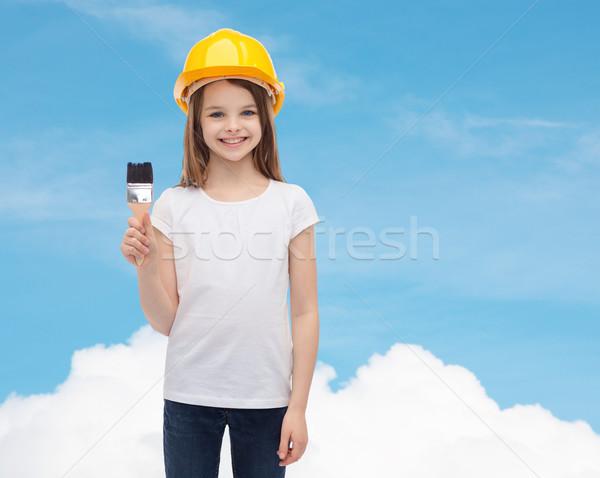 smiling little girl in helmet with paint roller Stock photo © dolgachov