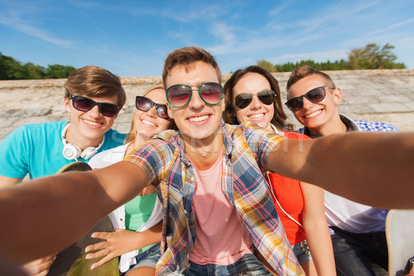 group of smiling friends making selfie outdoors Stock photo © dolgachov