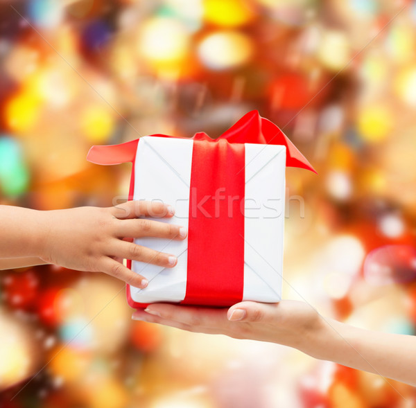 Stock photo: close up of child and mother hands with gift box