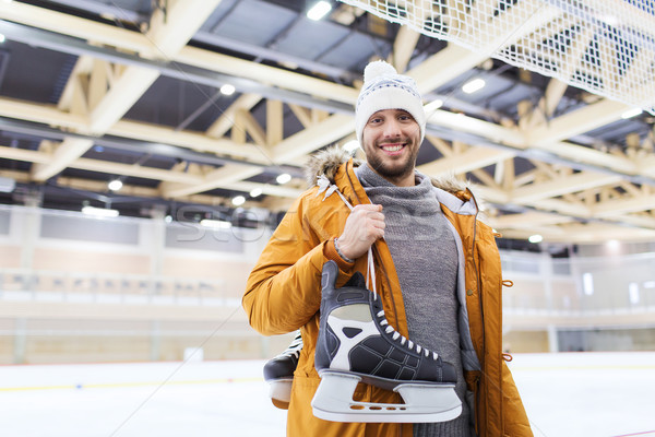 happy young man with ice-skates on skating rink Stock photo © dolgachov