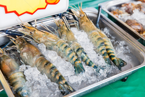 shrimps or seafood on ice at asian street market Stock photo © dolgachov