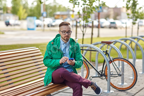 happy young hipster man with smartphone and bike Stock photo © dolgachov