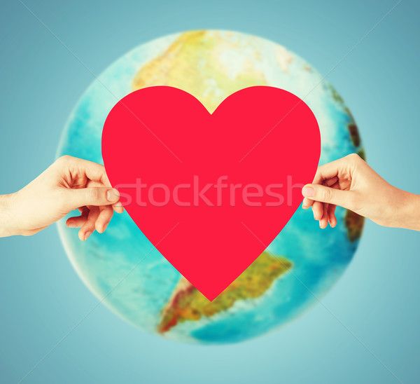 Stock photo: human hands holding red heart over earth globe